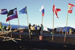GEN YAMAGUCHI / SPECIAL TO THE STAR-ADVERTISER                                 A group of protesters huddled Thursday near the campground along Saddle Road at the base of Mauna Kea.