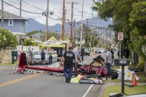 DENNIS ODA / April 30                                 Investigators inspect the wreckage on Oneawa Street in Kailua a day after a Robinson R44 sightseeing helicopter crashed, killing the pilot and two passengers.