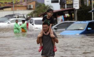 ASSOCIATED PRESS                                 A man carrying a boy wades through floodwaters at Jatibening on the outskirt of Jakarta, Indonesia, today. Severe flooding hit Indonesia's capital just after residents celebrating New Year's Eve, forcing a closure of an airport and thousands of inhabitants to flee their flooded homes.