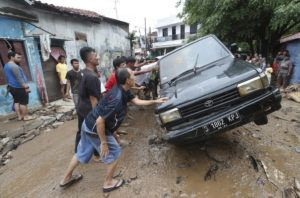 ASSOCIATED PRESS                                 Residents moved the wreckage of cars that were swept away by flooding in Bekasi, West Java, Indonesia, Friday. Severe flooding in greater Jakarta has killed scores of people and displaced tens of thousands of others, the country's disaster management agency said.