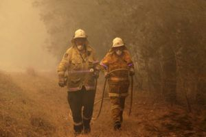 ASSOCIATED PRESS                                 Firefighters drag their water hose after putting out a spot fire near Moruya, Australia.