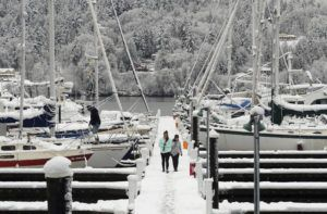 ASSOCIATED PRESS                                 Abbie Brown and Mallory Burns stroll along the snow-covered dock at the Poulsbo Marina in Poulsbo, Wash., today.