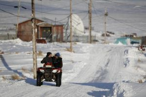 ASSOCIATED PRESS                                 People ride through town on all-terrain vehicles on Saturday in Toksook Bay, Alaska. The first Americans to be counted in the 2020 Census starting Tuesday live in this Bering Sea coastal village. The Census traditionally begins earlier in Alaska than the rest of the nation because frozen ground allows easier access for Census workers, and rural Alaska will scatter with the spring thaw to traditional hunting and fishing grounds.