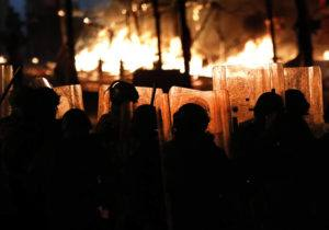 ASSOCIATED PRESS                                 Riot policemen watch flames rise from the tents of anti-government protesters, which where set on fire by civilian men believed to be the private unit of the parliament guards, during ongoing protests against the political elites who have ruled the country for decades, in Beirut, Lebanon, on Saturday. Riot police fired tear gas and sprayed water cannon near parliament in Lebanon's capital to disperse thousands of protesters after riots broke out during a march against the ruling elite amid a severe economic crisis.
