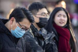 ASSOCIATED PRESS                                 Travelers wore face masks as they walked outside of the Beijing Railway Station in Beijing, Monday. China reported, Monday, a sharp rise in the number of people infected with a new coronavirus, including the first cases in the capital.