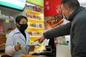 ASSOCIATED PRESS Staff sold masks at a Yifeng Pharmacy in Wuhan, Chin, Wednesday. Pharmacies in Wuhan are restricting customers to buying one mask at a time amid high demand and worries over an outbreak of a new coronavirus.
