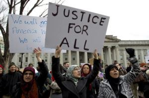 ASSOCIATED PRESS                                 Demonstrators carry signs chant as they protest outside of the White House in Washington during a demonstration to denounce President Donald Trump's executive order banning travel to the U.S. by citizens of Iraq, Syria, Iran, Sudan, Libya, Somalia and Yemen in 2017. Trump's travel ban on travelers from predominantly Muslim countries is headed back to a federal appeals court, three years after it was first imposed.