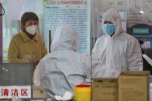 CHINATOPIX VIA AP                                 Medical workers in protective gear talk with a woman suspected of being ill with a coronavirus at a community health station in Wuhan in central China's Hubei Province.