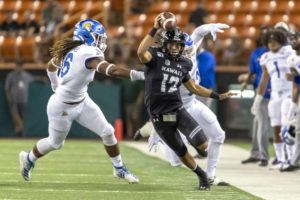 ASSOCIATED PRESS                                 Hawaii quarterback Chevan Cordeiro (12) tries to control his balance and cut back on to the field in the first half of an NCAA college football game on Nov. 9 in Honolulu.