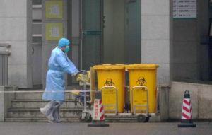 ASSOCIATED PRESS                                 A staff member moves biowaste containers past the entrance of the Wuhan Medical Treatment Center in Wuhan, China, on Wednesday.