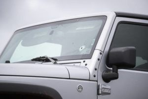 CINDY ELLEN RUSSELL / CRUSSELL@STARADVERTISER.COM                                 A bullet hole through the windshield of a Jeep was visible as it was towed from an access road near Whitmore Village today.