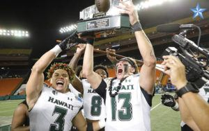 JAMM AQUINO / Dec. 24                                 Hawaii quarterback Cole McDonald (13) holds the championship trophy after winning the 2019 SoFi Hawaii Bowl college football game against the Brigham Young Cougars on Dec. 24 at Aloha Stadium.