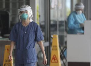 "ASSOCIATED PRESS                                 Hospital staff wear face protection at the Princess Margaret Hospital in Hong Kong. China's death toll from a new virus continues to rise as a World Health Organization official says other governments need to prepare for""domestic outbreak control"" if the disease spreads."