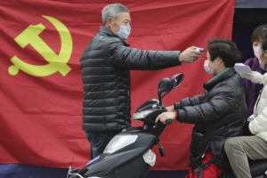CHINATOPIX VIA AP                                 A volunteer stands in front of a Communist Party flag as he takes the temperature of a scooter driver at a roadside checkpoint in Hangzhou in eastern China's Zhejiang Province today.