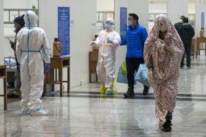 CHINATOPIX VIA ASSOCIATED PRESS Medical workers in protective suits helped patients, Wednesday, who were diagnosed with the coronavirus as they arrived at a temporary hospital, which was transformed from an exhibition center in Wuhan in central China's Hubei province.