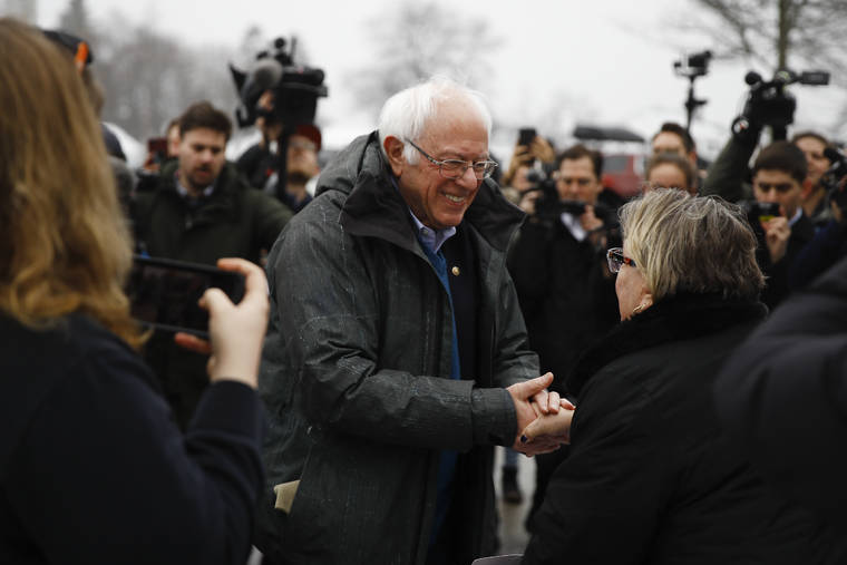 ASSOCIATED PRESS                                 Democratic presidential candidate Sen. Bernie Sanders, I-Vt., meets with people outside a polling place where voters will cast their ballots in a primary election in Manchester, N.H.