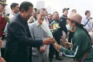 ASSOCIATED PRESS                                 Cambodia's Prime Minister Hun Sen, left, gives a bouquet of flowers to a passenger who disembarked from the MS Westerdam, owned by Holland America Line, at the port of Sihanoukville, Cambodia, Friday. Hundreds of cruise ship passengers long stranded at sea by virus fears cheered as they finally disembarked and were welcomed to Cambodia.