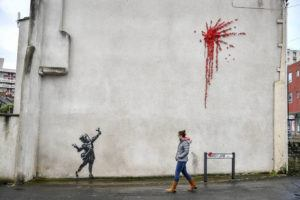ASSOCIATED PRESS                                 A woman walks past a new artwork on the side of a house in Bristol, England, on Feb. 13, which has been confirmed as the work of street artist Banksy.
