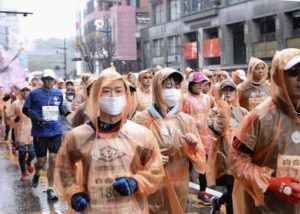 ASSOCIATED PRESS Runners, some wearing masks, compete in a Kumamoto castle marathon in Kumamoto city, western Japan, today. Organizers of the Tokyo Marathon, set for March 1, are drastically reducing the number of participants out of fear of the spread of the coronavirus from China. The general public is essentially being barred from the race.