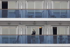ASSOCIATED PRESS                                 A passenger cleaned the window of his cabin on the quarantined Diamond Princess cruise ship on Feb. 15 in Yokohama. Two people from the quarantined cruise ship in Japan have died, NHK reported.