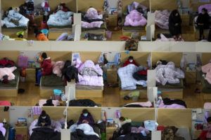 XINHUA VIA AP                                 Patients infected with the coronavirus take rest at a temporary hospital converted from Wuhan Sports Center in Wuhan in central China's Hubei Province.
