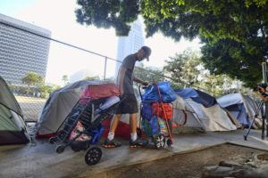ASSOCIATED PRESS                                 A homeless man moved his belongings, in July 2019, from a street near Los Angeles City Hall, background, as crews prepared to clean the area. Los Angeles city and county officials on Tuesday announced a new strategy to speed the process of getting homeless people into permanent housing that is modeled on the federal government's response to natural disasters.
