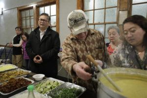 ASSOCIATED PRESS                                 Baptist Pastor Clifford Maung, third from left, recited a prayer, Sunday, as Chin Sai, center, and Myint Myint Swe, right, prepared food following services at the Overseas Burmese Christian Fellowship in Boston. All three are immigrants from Myanmar, also known as Burma.