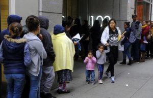 ASSOCIATED PRESS                                 Hundreds of people overflowed onto the sidewalk, in Jan. 2019, in a line snaking around the block outside a U.S. immigration office with numerous courtrooms in San Francisco. As the new public charge rule took effect, today, droves of immigrants including citizens and legal residents dropped government social services they or their children may be entitled to out of fear they will be kicked out of the U.S.