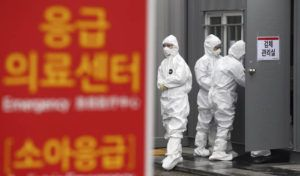 """KIM HYUN-TAE/YONHAP VIA ASSOCIATED PRESS                                 Officials wearing protective attire worked to diagnose people with suspected symptoms of the new coronavirus at a hospital in Daegu, South Korea, Wednesday. The number of new virus infections in South Korea jumped again Wednesday and the U.S. military reported its first case among its soldiers based in the Asian country, with his case and many others connected to a southeastern city with an illness cluster. A sign reads """"Emergency Medical Center."""""""