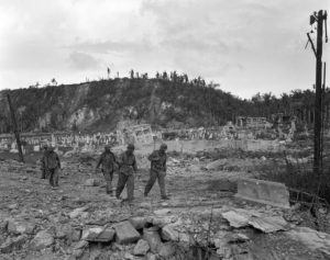 ASSOCIATED PRESS / AUG. 1944                                 U.S. soldiers walked by a bombed-out cemetery in Agana, Guam. The 1941 Japanese invasion of Guam, which happened on the same December day as the attack on Hawaii's Pearl Harbor, set off years of forced labor, internment, torture, rape and beheadings. Now, more than 75 years later, thousands of people on Guam, a U.S. territory, are expecting to get long-awaited compensation for their suffering at the hands of imperial Japan during World War II.