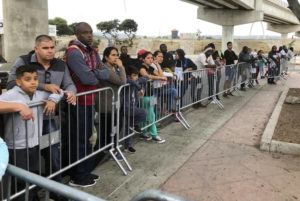 ASSOCIATED PRESS                                 Asylum seekers, in Tijuana, Mexico, listened to names being called, Sept. 26, from a waiting list to claim asylum at a border crossing in San Diego. A federal appeals court has temporarily halted a major Trump administration policy to make asylum seekers wait in Mexico while their cases wind through U.S. immigration courts.