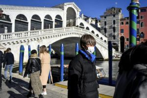 CLAUDIO FURLAN/LAPRESSE VIA AP A man wearing a protective mask walks past the Ponte di Rialto (Rialto Bridge) in Venice, Italy, Friday, Feb. 28, 2020. Authorities in Italy decided to re-open schools and museums in some of the areas less hard-hit by the coronavirus outbreak in the country which has the most cases outside of Asia, as Italians on Friday yearned for a return to normal life even amid fears that the outbreak could plunge the country's economy into recession.