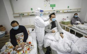 CHINATOPIX VIA ASSOCIATED PRESS                                 A doctor checked the condition of a patient in Jinyintan Hospital, designated for critical COVID-19 patients, in Wuhan in central China's Hubei province, Thursday. China on Thursday reported 254 new deaths and a spike in virus cases of 15,152, after the hardest-hit province of Hubei applied a new classification system that broadens the scope of diagnoses for the outbreak, which has spread to more than 20 countries.