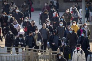 ASSOCIATED PRESS                                 Travelers wear face masks as they walk outside the Beijing Railway Station in Beijing on Saturday.