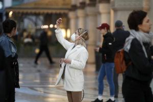 ASSOCIATED PRESS                                 A woman wearing sanitary mask takes a selfie in downtown Milan, Italy, on Sunday.