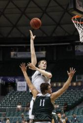 CINDY ELLEN RUSSELL / CRUSSELL@STARADVERTISER.COM                                 Dawson Carper (44) makes a basket over Mate Colina (11) during a University of Hawaii men's basketball scrimmage in October. Carper made the winning points tonight in UH's win over UC Riverside in California.