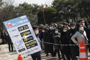 ASSOCIATED PRESS                                 An employee held a board listing face mask sales information as people lined up to buy face masks to protect themselves from the new coronavirus outside Nonghyup Hanaro Mart in Seoul, South Korea, Thursday. The number of infections of the COVID-19 disease spread around the globe.
