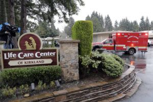 ASSOCIATED PRESS                                 An ambulance backs into a parking lot Friday at the Life Care Center in Kirkland, Wash.