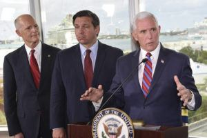 ASSOCIATED PRESS                                 Vice President Mike Pence, right, along with Florida Sen. Rick Scott, left, and Gov. Ron DeSantis, center, speaks to the media after a meeting with cruise line company leaders.