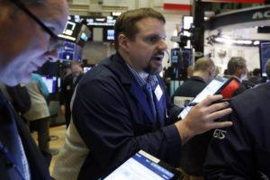 ASSOCIATED PRESS                                 Trader Michael Milano, center, works on the floor of the New York Stock Exchange on March 6.