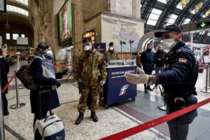 CLAUDIO FURLAN/LAPRESSE VIA ASSOCIATED PRESS                                 Police officers and soldiers checked passengers leaving from Milan's main train station, Italy, Monday. Italy took a page from China's playbook Sunday, attempting to lock down 16 million people — more than a quarter of its population — for nearly a month to halt the relentless march of the new coronavirus across Europe.