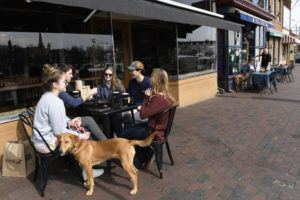 ASSOCIATED PRESS                                 Friends, from left, Erin Carroll of Severna Park, Md., Clay Colehouse of Crownsville, Md., Jessica Goblin of Severna Park, Md., Travis Victorio of Millersville, Md., Mary Fitzell of Millersville, Md., and dog Marty, enjoy lunch during a visit to Annapolis, Monday. Maryland Gov. Larry Hogan ordered the closure of bars, restaurants, gyms and movie theaters across the state in response to coronavirus beginning at 5 p.m. Monday. Drive-thru, carryout and delivery service will still be allowed. The friends gathered for lunch because they are home from college.