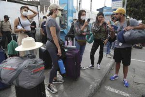 ASSOCIATED PRESS                                 Tourists from the United States wait outside the closed Jorge Chavez International Airport for a member of the U.S. Embassy to escort them to a flight that will fly them back to the U.S., in Callao Peru.
