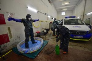 ASSOCIATED PRESS Volunteer workers of Search and Rescue (SAR) with special equipment, disinfect a volunteer while disinfecting police car at Local Police station to prevent the spread of coronavirus COVID-19, in Pamplona, northern Spain, today.