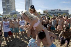 ASSOCIATED PRESS Cece Guida, 19, top, of New York City, pushes on Sam Reddick, 20, of Evansville, Ind., as spring break revelers look on during a game of chicken fight on the beach on March 17 in Pompano Beach, Fla. As a response to the coronavirus pandemic, Florida Gov. Ron DeSantis ordered all bars be shut down for 30 days beginning at 5 p.m. and many Florida beaches are turning away spring break crowds urging them to engage in social distancing.