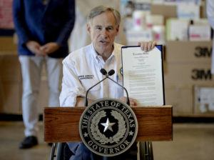 AUSTIN AMERICAN-STATESMAN VIA ASSOCIATED PRESS                                 Texas Gov. Greg Abbott shows a new executive order regarding reporting data about the coronavirus during a news conference on Tuesday in Austin, Texas.