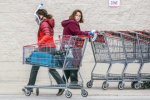 MICHAEL BRYANT/THE PHILADELPHIA INQUIRER VIA ASSOCIATED PRESS                                 A Costco employee, right, looked towards a shopper wearing a mask and snorkel to go shopping, as she sanitized carts that are returned from the parking lot to help reduce the spread of coronavirus, in King of Prussia, Pa., Wednesday.