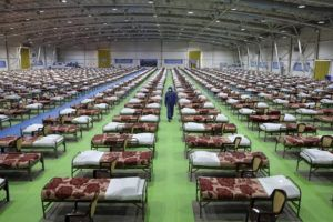 ASSOCIATED PRESS                                 A member of the Iranian army walks past rows of beds at a temporary 2,000-bed hospital for COVID-19 coronavirus patients set up by the army at the international exhibition center in northern Tehran, Iran, on Thursday.