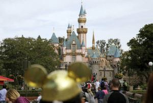 ASSOCIATED PRESS                                 Visitors walk toward Sleeping Beauty's Castle in the background at Disneyland Resort in Anaheim, Calif., in 2015. Disneyland says it's closing its California parks starting Saturday over coronavirus concerns.