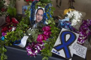 CRAIG T. KOJIMA / CKOJIMA@STARADVERTISER.COM Memorial of lei and flowers are seen in front of a portrait of Kaulike Kalama placed on a table under the HPD's Roll of Honor plaque, Jan. 22. Funeral services for Kalama will be held today at Kamehameha Schools Kapalama.
